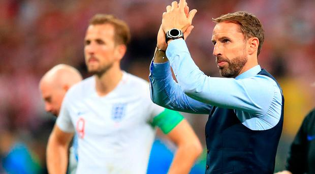 Bittersweet feeling: England boss Gareth Southgate leads the applause for his players despite their World Cup semi-final defeat to Croatia in Moscow