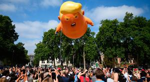 A 'Baby Trump' balloon rises after being inflated in London's Parliament Square, as part of the protests against the visit of US President Donald Trump to the UK. PRESS ASSOCIATION Photo. Picture date: Friday July 13, 2018. See PA story POLITICS Trump. Photo credit should read: Kirsty O'Connor/PA Wire