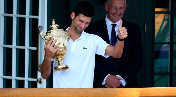 Novak Djokovic with the trophy on a centre court balcony after winning the Gentlemen's singles final on day thirteen of the Wimbledon Championships - Credit: Steven Paston/PA Wire.