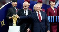 FIFA president Gianni Infantino, left, and Russian president Vladimir Putin with the World Cup trophy prior to the start of the presentation after the World Cup final (Owen Humphreys/PA)