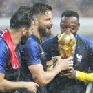 Olivier Giroud (centre right) with the trophy (Owen Humphreys/PA)