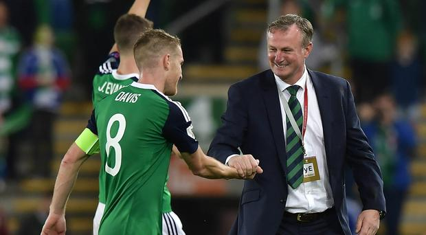 New chapter: NI boss Michael O'Neill wants more reason to celebrate with his skipper Steven Davis
