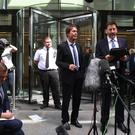 Sir Cliff Richard (centre) with his lawyer Gideon Benaim outside court (Victoria Jones/PA)