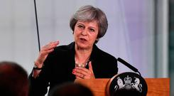 Tough talking: Theresa May gestures as she delivers a keynote speech on Brexit at the Waterfront Hall in Belfast yesterday