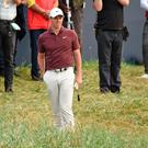Northern Ireland's Rory McIlroy waits in the rough beside the 18th green during his third round on day 3 of The 147th Open golf Championship at Carnoustie, Scotland on July 21, 2018. / AFP PHOTO / Paul ELLISPAUL ELLIS/AFP/Getty Images