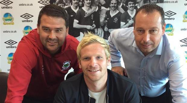 New signing Ryan McGivern in the Linfield boardroom with manager David Healy and chairman Roy McGivern. Credit: Linfield
