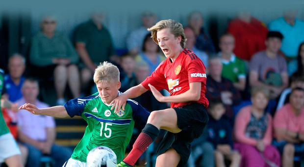 Like father like son: Club NI's Dylan Sloan wrestles with Manchester United's Charlie Savage