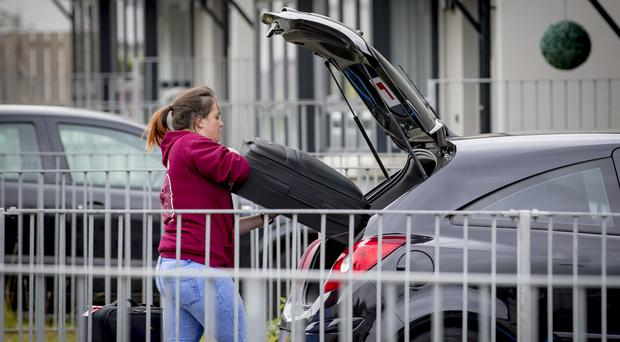 Families leave their homes with bags and suitcases
