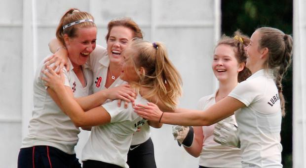All smiles: Lurgan captain Hannah Grieve (left) and player of the match Suzie McCollum (third left) lead the celebrations after another Civil Service North wicket in yesterday's Gallagher's Women's Challenge Cup final at Stormont which Lurgan won by two wickets