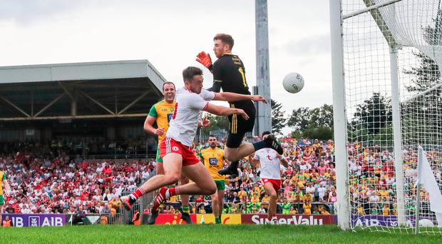 Golden moment: Tyrone's Harry Loughran scores his side's first goal despite Donegal goalkeeper Shaun Patton's best efforts yesterday