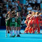 Fighting spirit: the Irish players embrace as The Netherlands team celebrates winning the trophy
