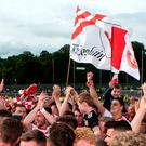 Flying the flag: Tyrone players celebrate victory with their fans on the pitch