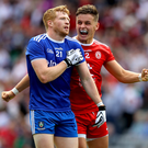 Joy and pain: Tyrone's Michael McKernan celebrates his side's first goal in front of Kieran Hughes