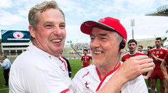 Final fling: Tyrone assistant manager Greg Devlin celebrates with manager Mickey Harte after the game at Croke Park yesterday