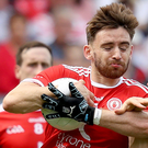 Standing firm: Tyrone's Padraig Hampsey holds off Vinney Corey