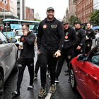 Striding on: Tyson Fury and his entourage arrive at the Europa Hotel in Belfast