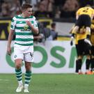 Sinking feeling: Celtic's James Forrest looks dejected as AEK Athens players celebrate their second goal of the night