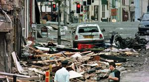 UK USE ONLY File photo dated 15/08/1998 of a police officer looking at the damage caused by a bomb explosion in Market Street, Omagh. Paul McErlane/Press Association.