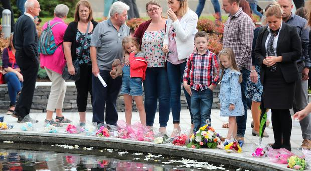 People visit the Omagh Memorial garden after attending the ceremony for victims of the car bomb on Market Street on the 15th August 1998. Photo credit should read: Niall Carson/PA Wire