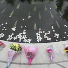 White rose petals are thrown into a pond at the Omagh Memorial garden (Niall Carson/PA)