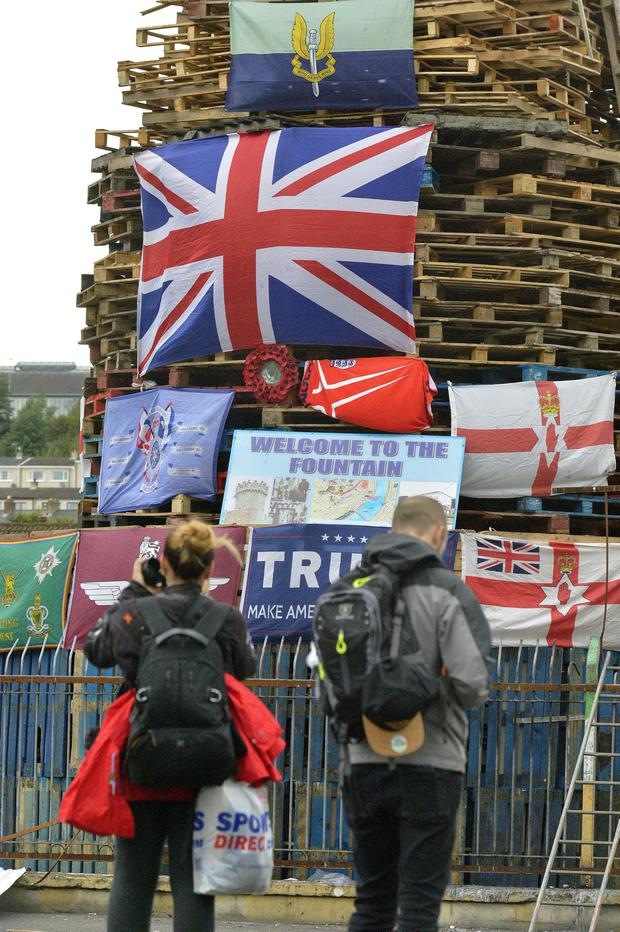 Tourists photograph flags on a controversial bonfire, in the Bogside area of Londonderry, which is traditionally torched on August 15. Credit: George Sweeney