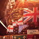 The bonfire, containing placards carrying the names of dissident victims and poppy wreaths, is lit