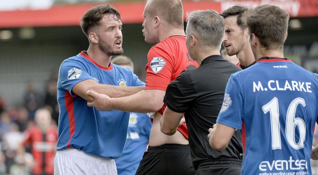 Linfield's Josh Robinson (left) came in for a rough reception from the Crusaders fans on Saturday afternoon, responding on several occasions by tapping the Linfield badge on his chest.