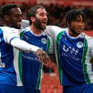 Wigan Athletic's Will Grigg (centre) celebrates with Gavin Massey (left) and Reece James.
