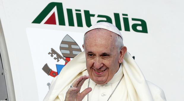 Pope Francis waves as he boards his flight to Ireland at Rome's Fiumicino international airport (Andrew Medichini/AP)