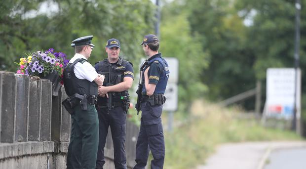 Members of the PSNI and the Gardai stand exactly on the border in Belleek, County Fermanagh (Niall Carson/PA)