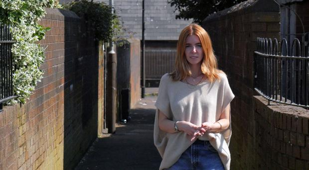 Stacey Dooley standing at an alleyway in the Divis Estate, Belfast, where a young man was shot four times in the legs. Photographer: Joseph McAuley.