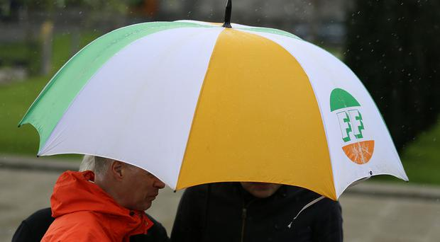 A Fianna Fail umbrella as party leader Micheal Martin hints at a merger with the SDLP (Brian Lawless/PA)
