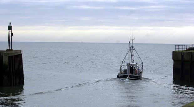 Undated file photo of a fishing boat leaving Kilkeel harbour in Ulster. The Northern Ireland fishing fleet could be decimated this week when European Ministers meet in Brussels on Monday December 16 2002, to discuss fishing quotas for next year. Fishermen in the province fear fishing for cod, haddock and other white fish could be a thing of the past unless the EU relaxes its plans. Local people going to the fish and chip shop would end up buying a fish supper in which the fish came from as far afield as Russia, they warn. Pearson, the Northern Ireland minister responsible for Agriculture and Fisheries, is attending the cruch meetings to fight the corner of local fishermen. See PA story ULSTER Fish. PA Photo