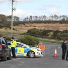 Gardai outside Drummond Mine in County Monaghan where a suspected mine collapse has caused major sinkholes to appear at a nearby sports field (Niall Carson/PA)