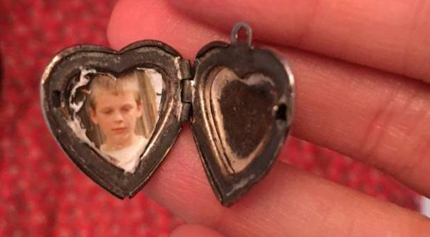 A woman who found a silver locket in a charity shop dress is looking to reunite it with its owner.