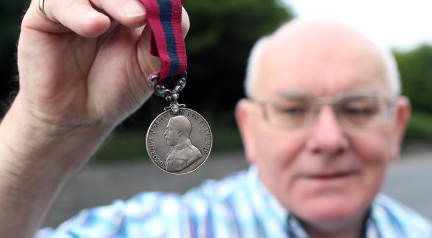John Bannon holds a medal awarded to his grandfather Jack Bannon