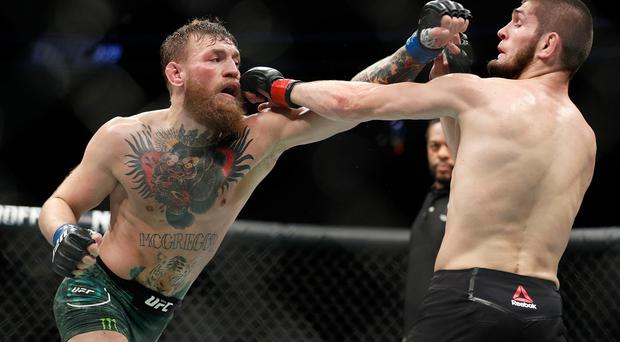 Conor McGregor, left, and Khabib Nurmagomedov throw punches during a lightweight title mixed martial arts bout at UFC 229 in Las Vegas, Saturday, Oct. 6, 2018. (AP Photo/John Locher)