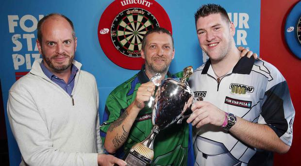 Nigel Cahoon (centre) receives the inaugural Four Star Pizza NI Darts Challenge trophy from World number five Daryl Gurney (right) and Four Star Pizza director Brian Clarke.