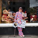 WINDSOR, ENGLAND - OCTOBER 12: Royal fan Terry Hutt dresses up in the Union Jack flag holding a sign of congratulations ahead of the Royal wedding of Princess Eugenie of York and Mr. Jack Brooksbank at St. George's Chapel on October 12, 2018 in Windsor, England. (Photo by Leon Neal/Getty Images)