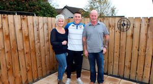 Middle man: Coleraine star Josh Carson with mum Elaine and dad Glyn