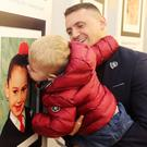 Jamie Brown with his son Bodhi (2) pictured beside a picture of their relative Michelle Baird (7) who was killed in the bomb. Picture by Jonathan Porter/PressEye