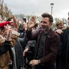 Shane Filan high fives a fan as he walks with band member, Kian Egan and Markus Feehily of Westlife at the SSE Arena, Belfast, ahead of the press conference for tickets going on sale for their reunion tour