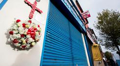 A wreath laid by Girls Model Head Girl Caitlin Herron hangs to the side of what was Frizzell's fish shop after a service at West Kirk Presbyterian Church in Belfast to mark the 25th anniversary of the IRA bombing of a fish shop on Shankill Road. Liam McBurney/PA Wire