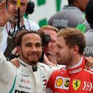 Five-star Lewis: Mercedes' Lewis Hamilton (left) waves at the crowd as he hugs Ferrari's German driver Sebastian Vettel
