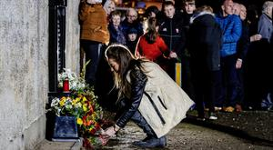 A woman lays a floral tribute during a vigil outside the Rising Sun pub in Greysteel. Liam McBurney/PA Wire