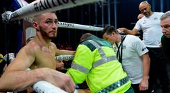 Ryan Burnett is treated by paramedics after he retired with a back injury on Saturday night.