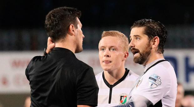 Seeing red: Referee Ian McNabb is confronted by Glentoran players at Solitude