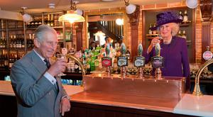 (FILES) In this file photo taken on October 27, 2016 Britain's Camilla, Duchess of Cornwall (R) and Prince Charles, Prince of Wales (L) drink a half pint of