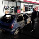 SDLP Councillor Brian Tierney pictured with the burnt out car.