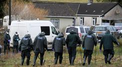 Police officers and police forensic experts examine a murder scene in County Fermanagh today - A 59-year-old woman murdered in Enniskillen has been described as